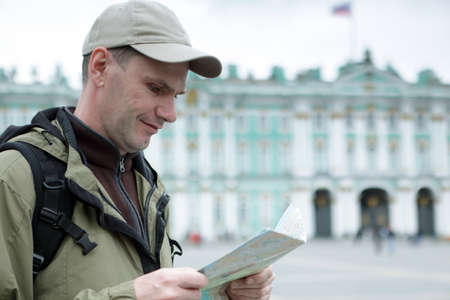 st petersburg: Tourist with a map against Winter Palace in St. Petersburg