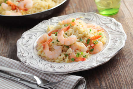 prepared shrimp: Risotto with shrimps and green onion on a rustic table