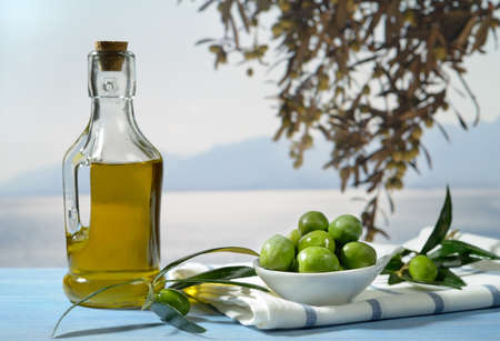 Olives and olive oil against Mediterranean landscape