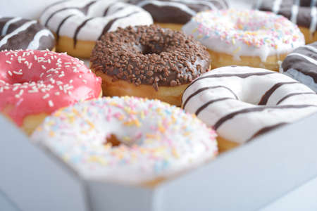 Assorted sweet donuts in a paper box. Shallow DOF photo