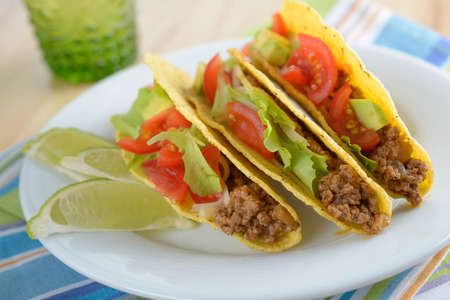 prepared food: Tacos with ground beef and vegetables on a plate
