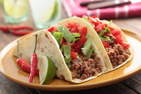 Tacos with ground beef and vegetables on a rustic table photo