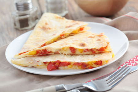 Three wedges of quesadilla on a plate photo