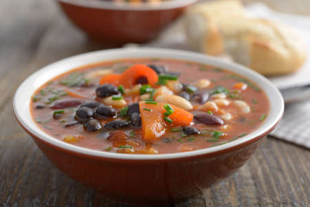 Three bean soup on a rustic table photo
