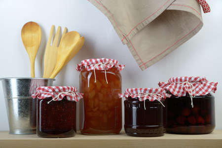 Jars with homemade jam on a shelf photo