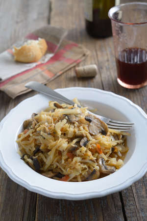 braised mushrooms: Braised cabbage with mushrooms and carrot on a rustic table
