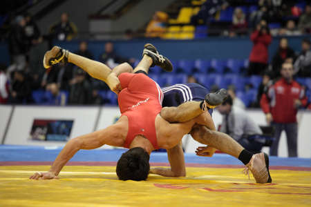 Kiev, Ukraine - February 16, 2013: Match between Zurabi Iakobishvili, Georgia, red and Azamat Kabisov, Russia during XIX International freestyle wrestling and female wrestling tournament in Kiev, Ukraine on February 16, 2013 Stock Photo - 17985574
