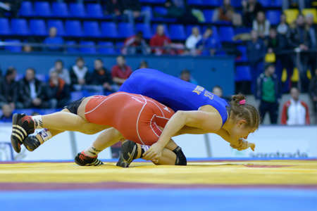 female wrestling: Kiev, Ukraine - February 16, 2013: Match between Emese Barka, Hungary, red and Larysa Skobliuk, Ukraine during XIX International freestyle wrestling and female wrestling tournament in Kiev, Ukraine on February 16, 2013