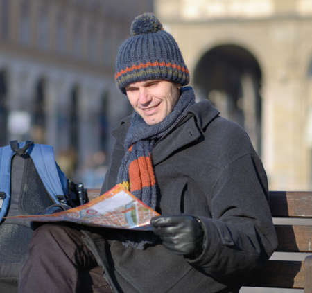Tourist with city plan on a bench at winter Stock Photo - 18562806