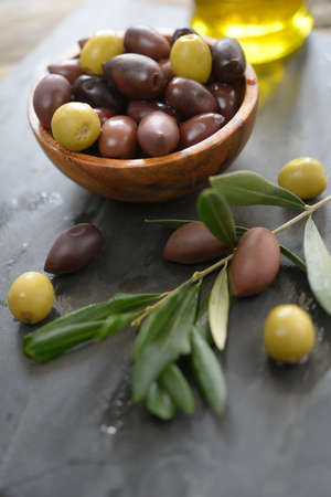 Marinated olives in a bowl on slate board photo