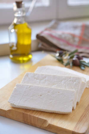 Feta cheese on a cutting board against olives and olive oil photo