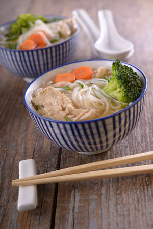 Asian chicken soup with rice noodles and vegetables photo