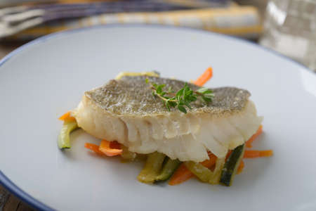 Baked cod on vegetable bed Imagens