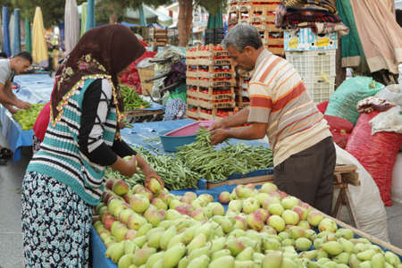 Kusadasi, Turkey - August 19, 2011: Farmers prepares to the new day on the street market in Kusadasi, Turkey on August 19, 2011