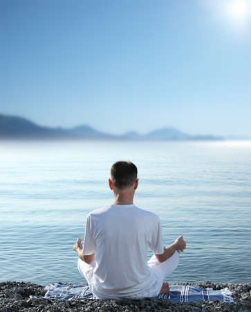 Mature man meditating on the beach photo