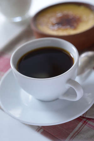 crema: Cup of black coffee and Crema catalana in a pot. Selective focus on a front edge of cup