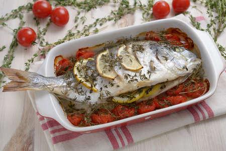 gilt head: Baked gilt head sea bream with lemon, thyme, and cherry tomatoes Stock Photo