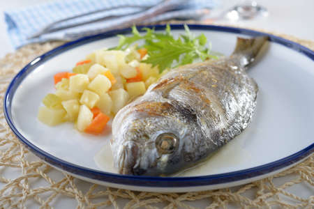 Baked sea bream with  potato, carrot, and celery photo