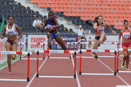 Donetsk, Ukraine - July 11, 2013: Girls compete in semi-final of 400 m hurdles during 8th IAAF World Youth Championships in Donetsk, Ukraine on July 11, 2013. Left to right: Bryannill Cardona, Venezuela, Tatiana Sanchez, Colombia, Nenah De Coninck, Belgiu