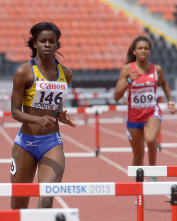 Donetsk, Ukraine - July 11, 2013: Tia-Adana Belle of  Barbados (left) and Klerianne Etanislao of Puerto Rico compete in semi-final of 400 m hurdles during 8th IAAF World Youth Championships in Donetsk, Ukraine on July 11, 2013