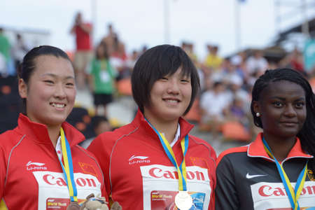 Donetsk, Ukraine - July 11, 2013: Medalists in  Discus Throw on 8th IAAF World Youth Championships in Donetsk, Ukraine on July 11, 2013. Left to right: Xinyun Liang, Yuchen Xie, both - China, Claudine Vita, Germany 新聞圖片