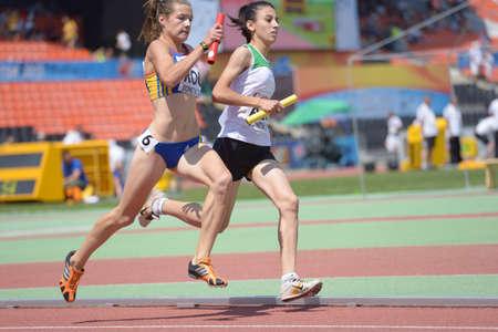 medley: Donetsk, Ukraine - July 13, 2013: Elena Strutinschi, Romania (left), and Sabrina Hocine, Algeria, compete in the medley relay during World Youth Championships in Donetsk, Ukraine on July 13, 2013