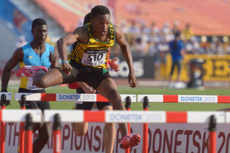 Donetsk, Ukraine - July 12, 2013: Jaheel Hyde of Jamaica and Xavier Coakley of Bahamas (left) compete in semi-final of 110 m hurdles during 8th IAAF World Youth Championships in Donetsk, Ukraine on July 12, 2013 Redakční