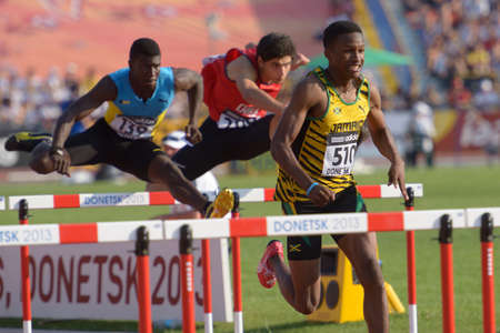 Donetsk, Ukraine - July 12, 2013: Jaheel Hyde of Jamaica (right), Xavier Coakley of Bahamas (left), and Diego del Monaco of Chile compete in semi-final of 110 m hurdles during 8th IAAF World Youth Championships in Donetsk, Ukraine on July 12, 2013