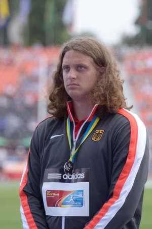 lanzamiento de disco: Donetsk, Ucrania - 14 de julio 2013: Medalla de plata en lanzamiento de disco Henning Prufer de Alemania en la ceremonia de premiaci�n durante el octavo Campeonato Mundial Juvenil de la IAAF en Donetsk, Ucrania el 14 de julio 2013 Editorial