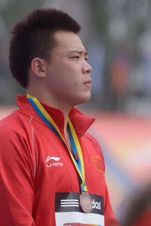 lanzamiento de disco: Donetsk, Ucrania - 14 de julio 2013: medalla de bronce en lanzamiento de disco Yulong Cheng de China durante la ceremonia de la medalla octavo Campeonato Mundial Juvenil de la IAAF en Donetsk, Ucrania el 14 de julio 2013