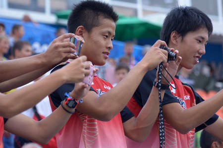 medley: Donetsk, Ukraine - July 14, 2013: Japanese fans make photos after the final round of medley relay during 8th IAAF World Youth Championships in Donetsk, Ukraine on July 14, 2013