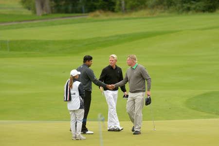 caddie: Moscow, Russia - July 27, 2013: Peter Hedblom of Sweden (center), Richard Finch of England (right), and Gaganjeet Bhullar of India with his caddie handshake during 3rd round of the M2M Russian Open at Tseleevo Golf & Polo Club in Moscow, Russia on July 27 Editorial