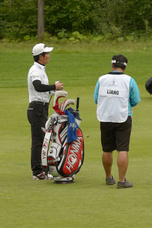 caddie: Moscow, Russia - July 28, 2013: Wen-chong Liang of China with his caddie during final round of the M2M Russian Open at Tseleevo Golf & Polo Club in Moscow, Russia on July 28, 2013 Editorial