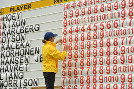 corrects: Moscow, Russia - July 28, 2013: Girl corrects the leaderboard during final round of the M2M Russian Open at Tseleevo Golf & Polo Club in Moscow, Russia on July 28, 2013