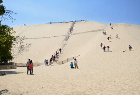 Pilat, France - June 27, 2013: People visit the dune of Pilat, France on June 27, 2013. This dune is the biggest one in Europe, and it still grow Stock Photo - 21674590