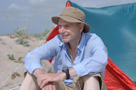 Man sitting on a beach against a tent photo