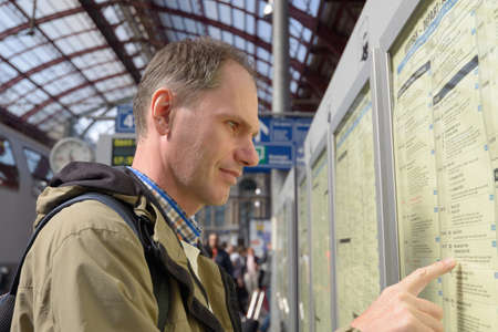 ceased: Antwerpen, Belgium - June 23, 2013  Passenger search the train in the timetable on the central train station of Antwerpen, Belgium on June 23, 2013  After reconstruction completed in 2007, the station ceased to be a terminus
