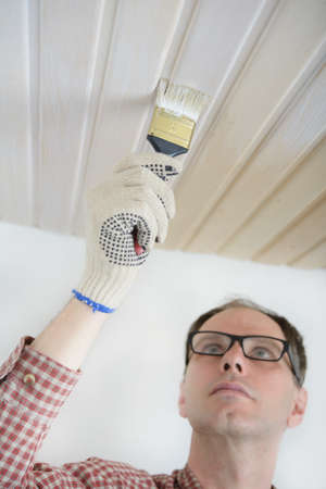 Nerd varnishing wooden panels on a ceiling photo