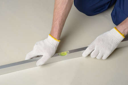 leveling: Construction worker measures the quality of floor using spirit level Stock Photo