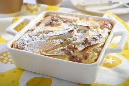 powdered sugar: Apple clafoutis with raisins and powdered sugar in a baking dish