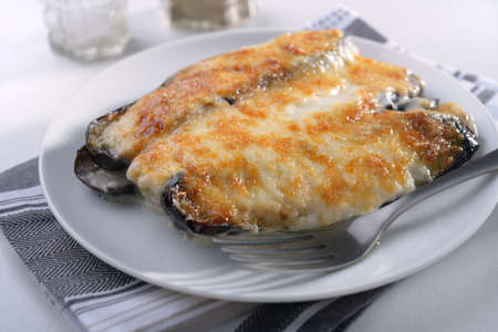 cuisines: Moussaka under white sauce on a plate