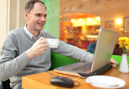 Man with laptop drinking coffee in a cafe photo