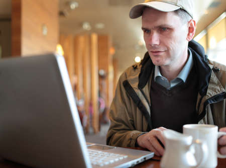 Mature man with laptop in a cafe photo