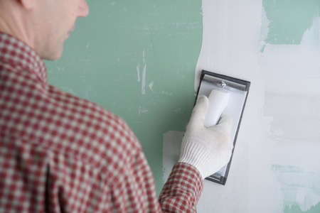 sanding: Contractor sanding the drywall mud using sand trowel