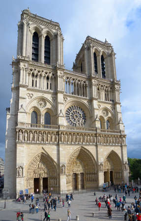 wor: Paris, France - September 11, 2013: Tourists under the building of Notre-Dame de Paris. The cathedral is widely considered to be one of the finest examples of French Gothic architecture and among the largest and most well-known church buildings in the wor