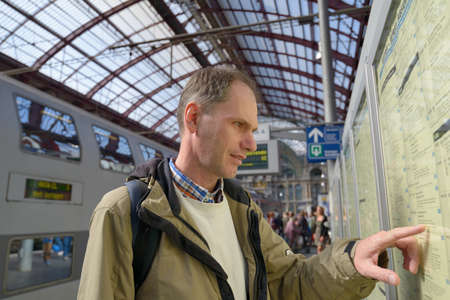 Passenger search the train in the timetable on the central train station of Antwerp, Belgium photo
