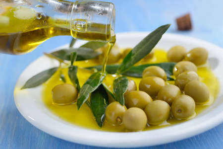 Pouring olive oil into the bowl with green olives photo