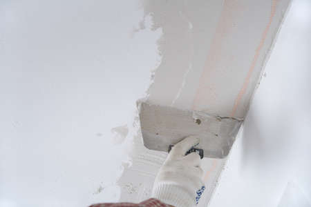 Contractor plastering a ceiling using plaster net photo