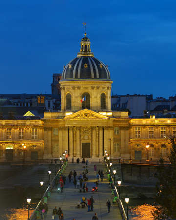 housed: Paris, France - September 11, 2013: People walking on the Pont des arts in front of the Institut de France. Since 1805, the Institut is housed in the building of the College of the Four Nations built in 1662-1688