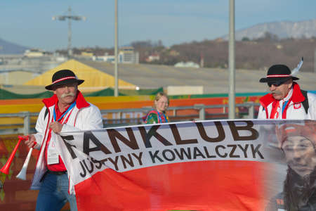 Sochi, Russia - February 12, 2014: Polish fans of Justyna Kowalczyk with flag in Olympic park. Next day Kowalczyk became Olympic champion in 10 km Classic ski race